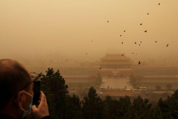 Návštěvník na vyhlídkové plošině během písečné bouře v Pekingu.  - Sputnik Česká republika