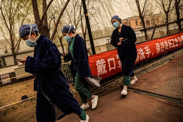 Zdravotní sestry během písečné bouře v Pekingu.  - Sputnik Česká republika
