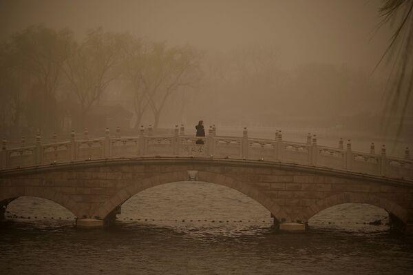 Dívka na mostě přes jezero Chou-chaj během písečné bouře v Pekingu.  - Sputnik Česká republika