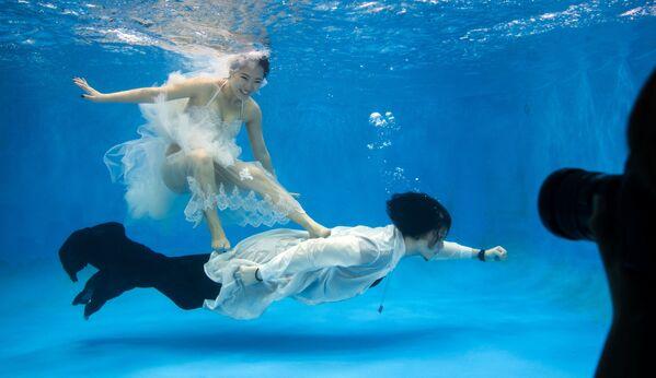 Novomanželé pózují pod vodou v Šanghaji v Číně.  - Sputnik Česká republika