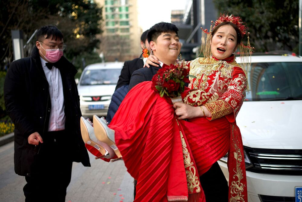 Ženich nese nevěstu do hotelu po svatbě ve Wu-chanu v Číně