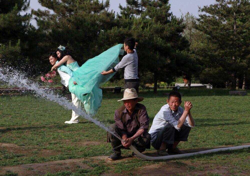 Novomanželé pózují v parku v Pekingu v Číně