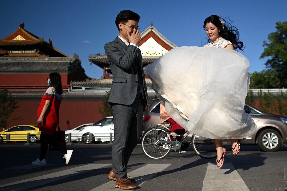 Pár pózuje během svatebního focení před Chrámem v Pekingu