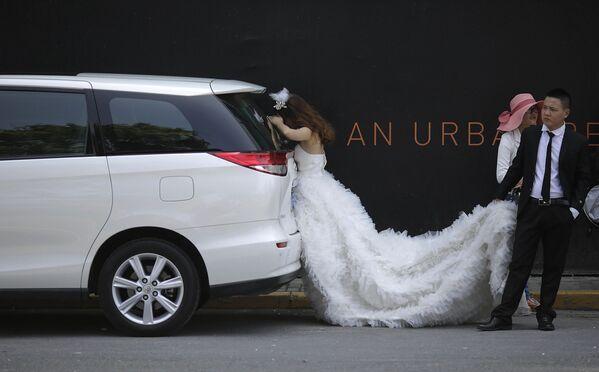 Nevěsta relaxuje ve stínu během svatebního focení v Šanghaji.  - Sputnik Česká republika