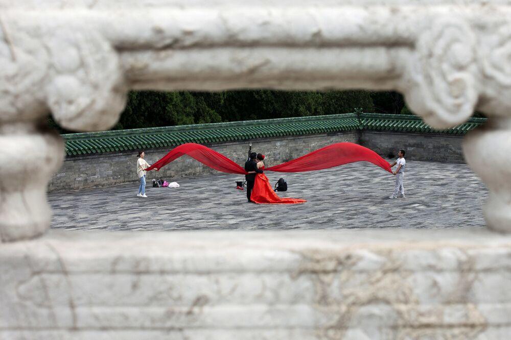 Pár během svatebního focení na náměstí před Chrámem nebes v Pekingu