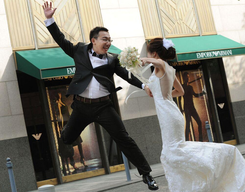 Ženich skáče vedle nevěsty během svatebního focení v Šanghaji