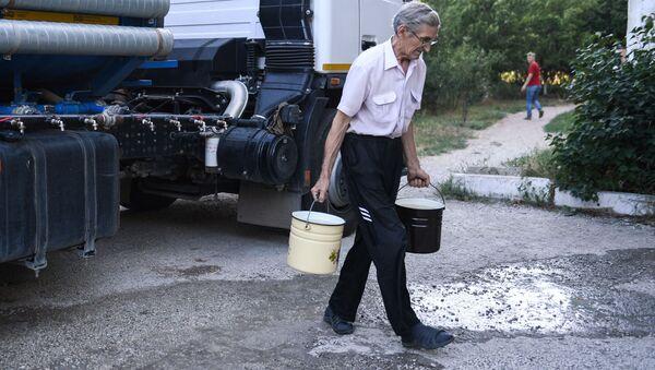 Obyvatel Simferopolu nese sladkou vodu, kterou přivezli v cisternách - Sputnik Česká republika