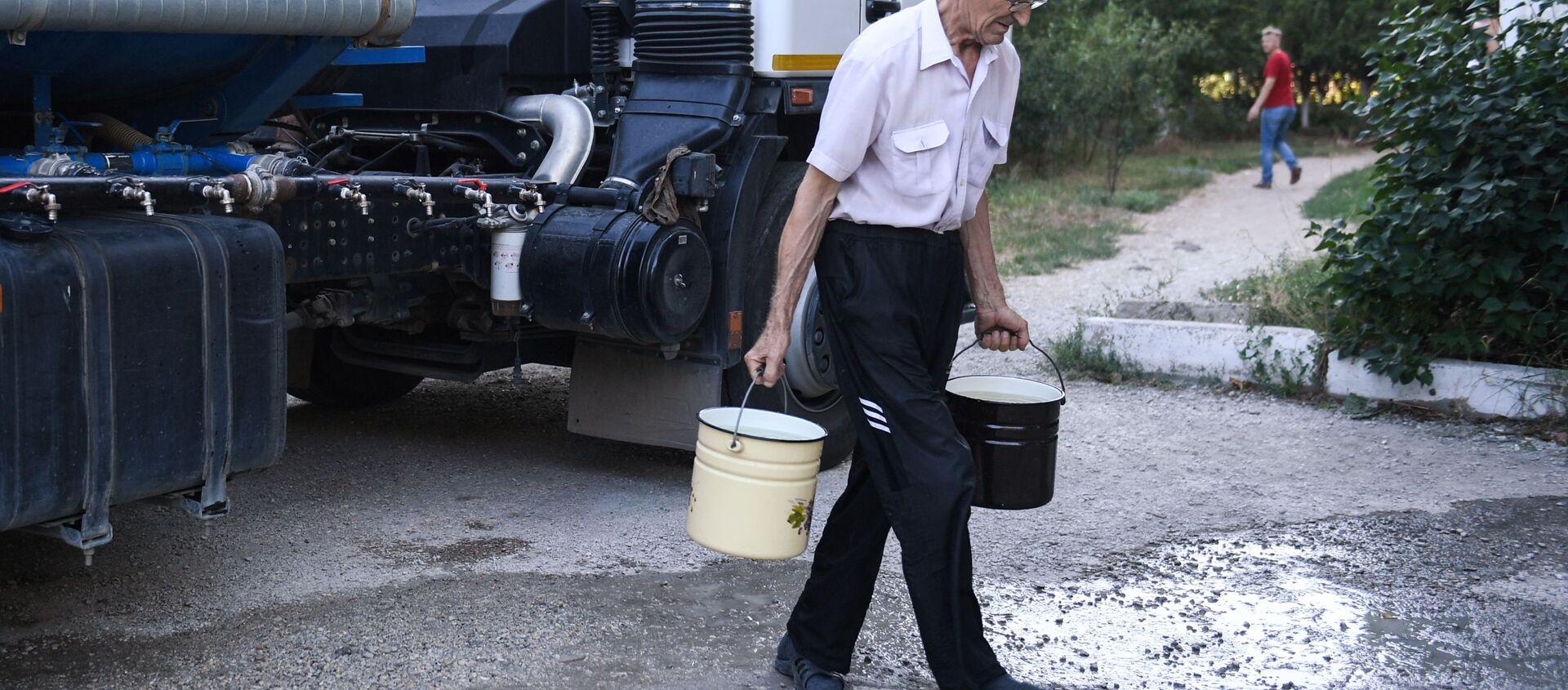 Obyvatel Simferopolu nese sladkou vodu, kterou přivezli v cisternách - Sputnik Česká republika, 1920, 18.03.2021