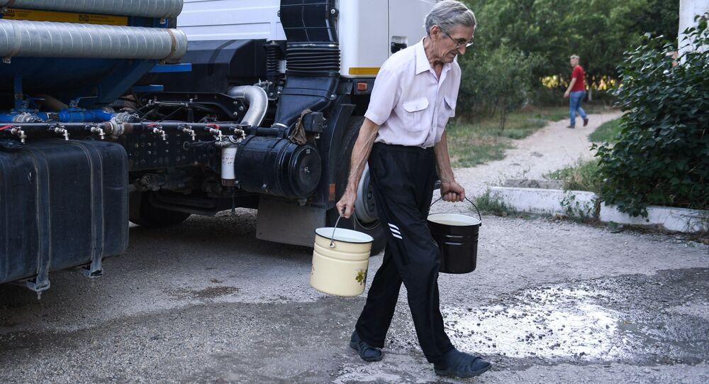 Obyvatel Simferopolu nese sladkou vodu, kterou přivezli v cisternách