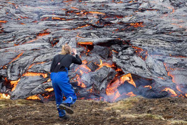 Muž se dívá na lávu po sopečné erupci na Islandu - Sputnik Česká republika