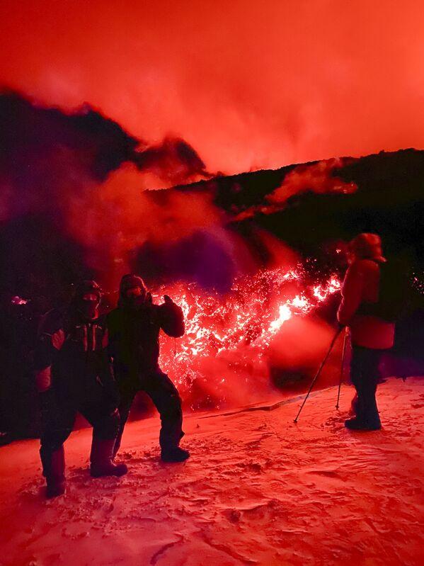 Turisté pózují na fotku během erupce sopky Ključevskaja na poloostrově Kamčatka v Rusku - Sputnik Česká republika