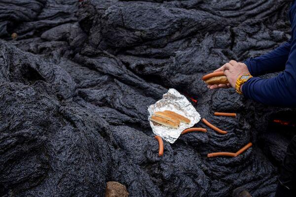Muž připravuje párky v rohlíku na vulkanickém místě na poloostrově Reykjanes po sopečné erupci na Islandu - Sputnik Česká republika