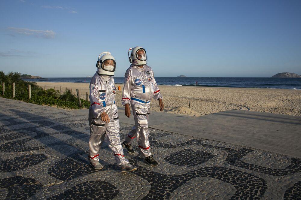 Dvojice oblečená v kostýmech astronautů se prochází po pláži Ipanema v Riu de Janeiro, Brazílie.