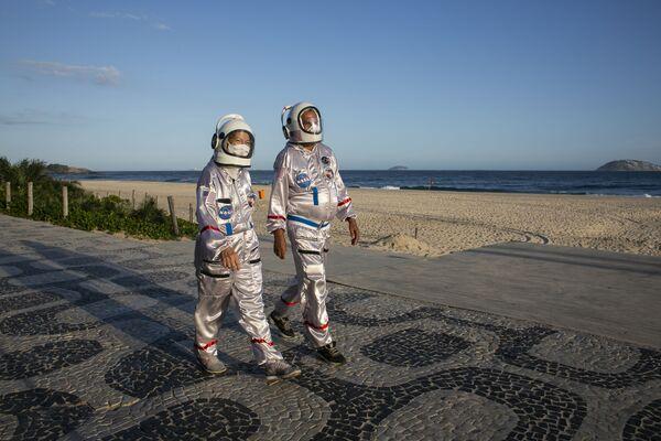 Dvojice oblečená v kostýmech astronautů se prochází po pláži Ipanema v Riu de Janeiro, Brazílie. - Sputnik Česká republika