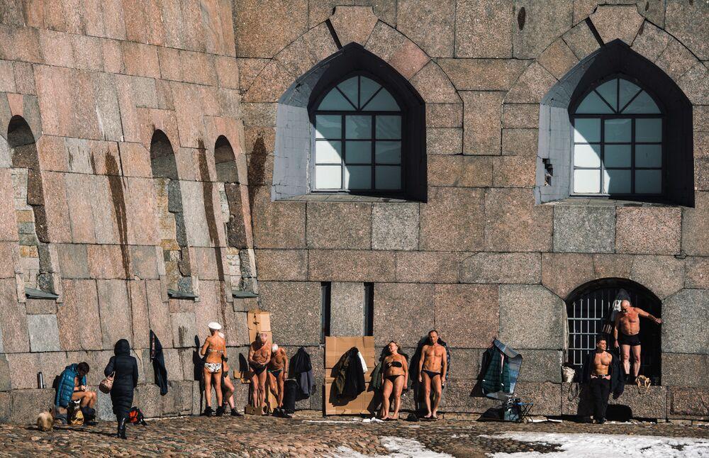 Lidé se opalují u zdi Petropavlovské pevnosti v Petrohradě.