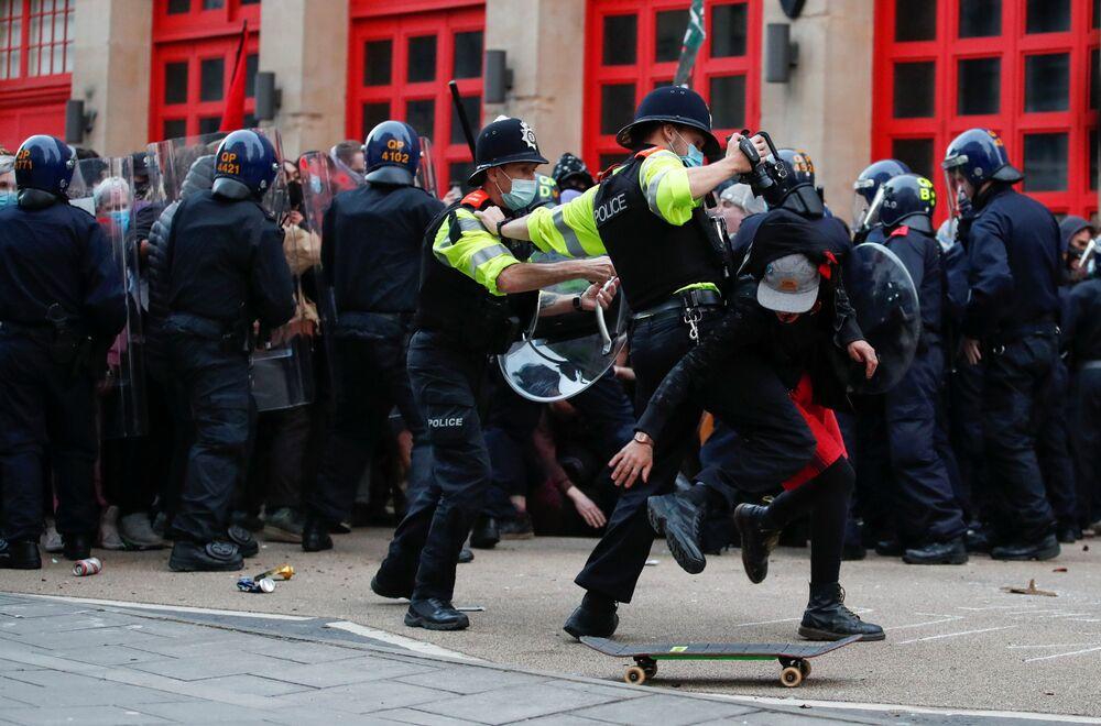 Policisté se snaží zadržet demonstranta během protestu v Bristolu, Velká Británie.