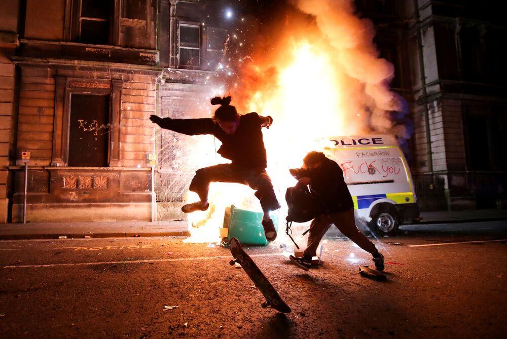 Demonstrant ujíždí na skateboardu před hořícím policejním autem při protestu v Bristolu, Velká Británie.