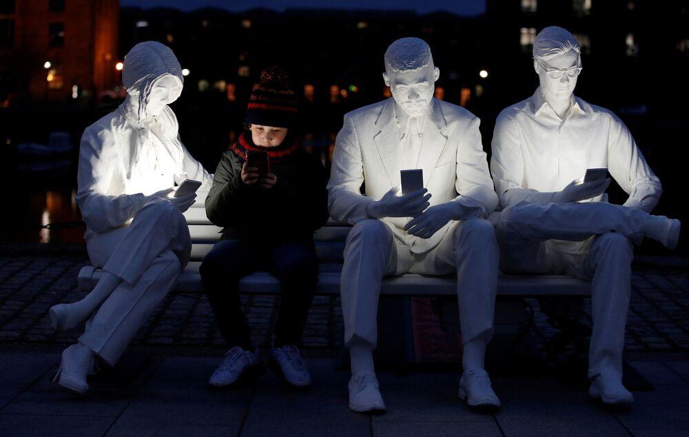 """Chlapec pózuje se sochou """"pohlceni světlem"""" vytvořenou umělcem Gali May Lucasem v Liverpoolu, Velká Británie."""