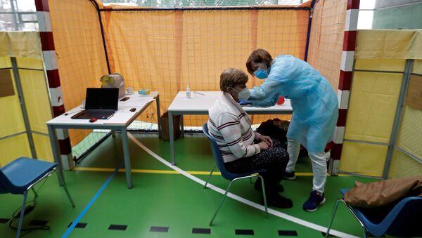 Zdravotník očkuje ženu proti koronaviru v centru hromadné vakcinace v tělocvičně v Praze - Sputnik Česká republika