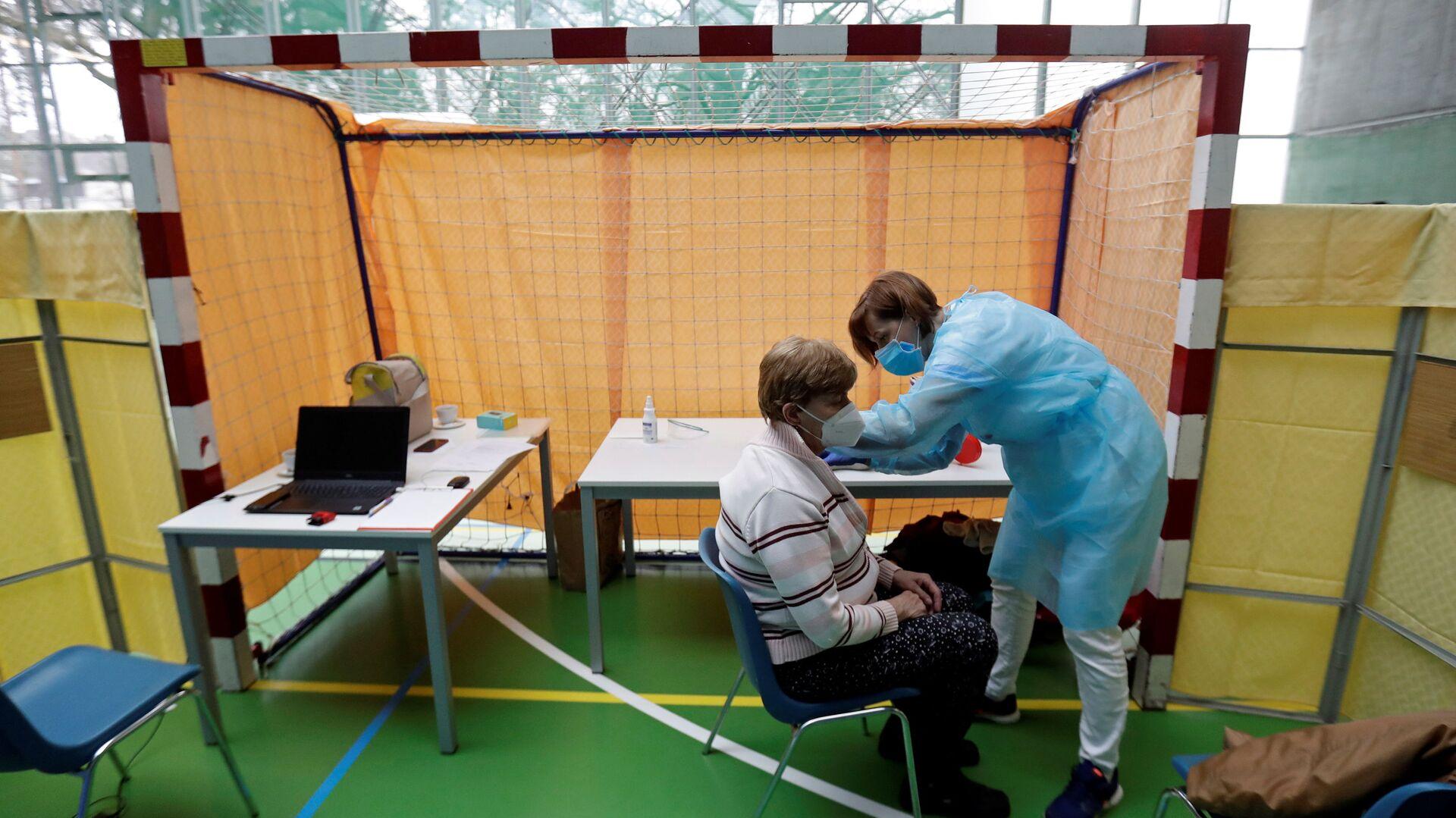 Zdravotník očkuje ženu proti koronaviru v centru hromadné vakcinace v tělocvičně v Praze - Sputnik Česká republika, 1920, 30.03.2021