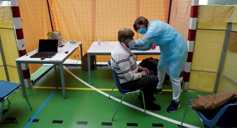 Zdravotník očkuje ženu proti koronaviru v centru hromadné vakcinace v tělocvičně v Praze
