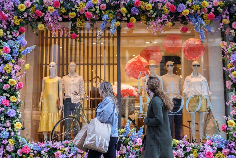 Potenciální zákazníci si prohlíží nové jarní kolekce představené ve výlohách obchodů na Manhattanu.