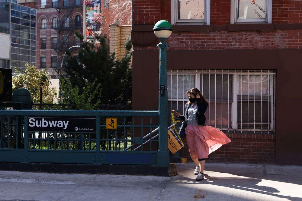 Mladá obyvatelka New Yorku vychází z metra a užívá si jarní počasí.