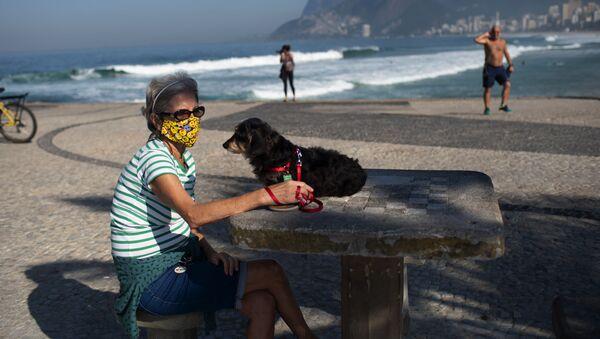 Žena v roušce se psem na pláži v Rio de Janeiru - Sputnik Česká republika