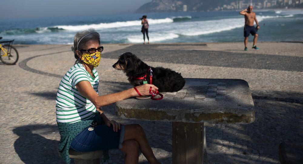 Žena v roušce se psem na pláži v Rio de Janeiru