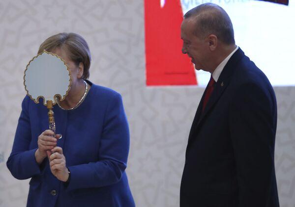 Německá kancléřka Angela Merkelová se baví se zrcadlem, které dostala jako dárek od tureckého prezidenta Recepa Tayypa Erdogana v Istanbulu v roce 2020. - Sputnik Česká republika