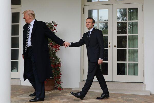 Americký prezident Donald Trump ze srandy vede za ruku francouzského prezidenta Emmanuela Macrona v Bílém domě v roce 2018.  - Sputnik Česká republika