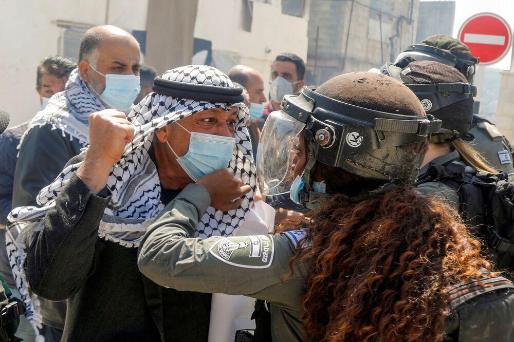 Palestinský demonstrant se pere se ženou z pohraniční stráže během protestní akce