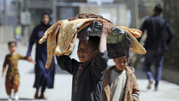 Мальчик с хлебом на голове на одной из улиц Кабула, Афганистан - Sputnik Česká republika