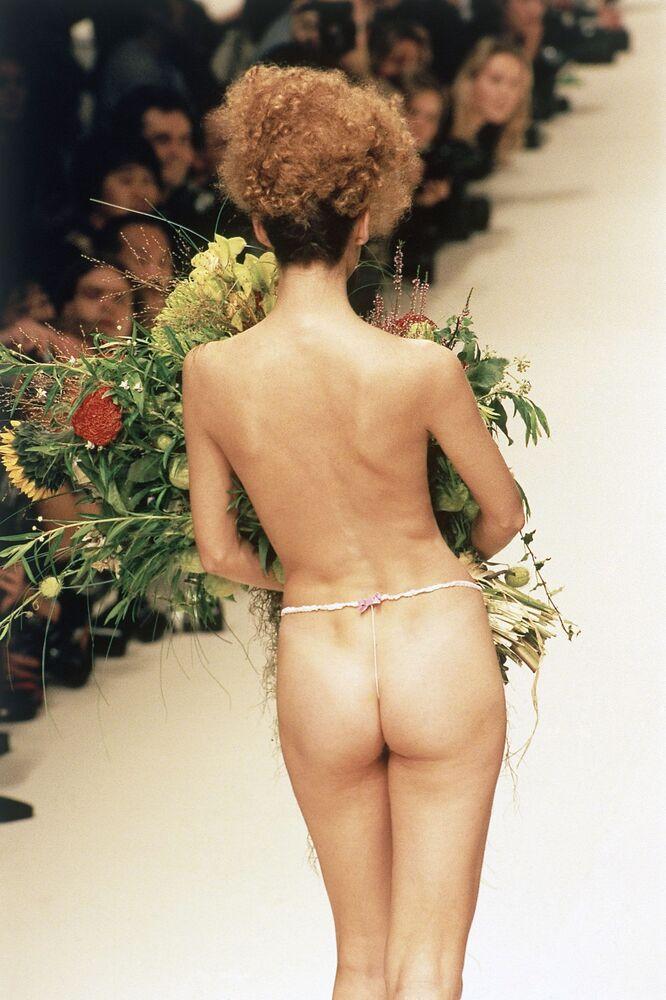 Modelka v tangách s kyticí květů během přehlídky kolekce Vivienne Westwoodové jaro-léto 1995, která se konala v Paříži.