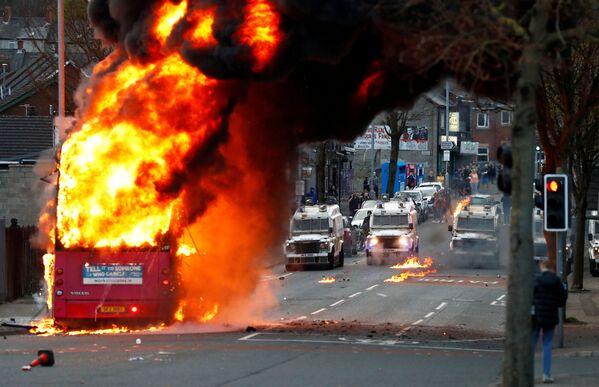 Hořící autobus na Shankill Road během protestů v Belfastu v Severním Irsku  - Sputnik Česká republika