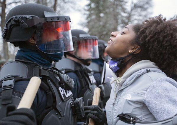 Účastnice protestu a policisté v centru města Brooklyn Center v Minnesotě. - Sputnik Česká republika