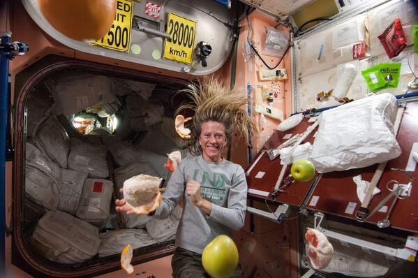 Americká Astronautka NASA Karen Nybergová s volně plujícím čerstvým ovocem ve stavu beztíže na palubě mezinárodní vesmírné stanice.  - Sputnik Česká republika