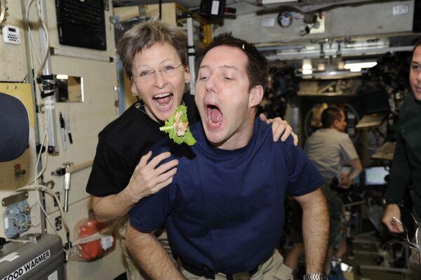 Francouzský astronaut Toma Pesce a astronautka NASA Peggy Whitsonová loví svačinu na palubě mezinárodní vesmírné stanici. - Sputnik Česká republika