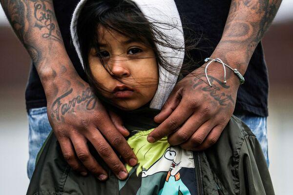 Obyvatel Brooklynu se svoji tříletou dcerou během protestu kvůli smrti Wrighta před policejním oddělením v Minnesotě.  - Sputnik Česká republika