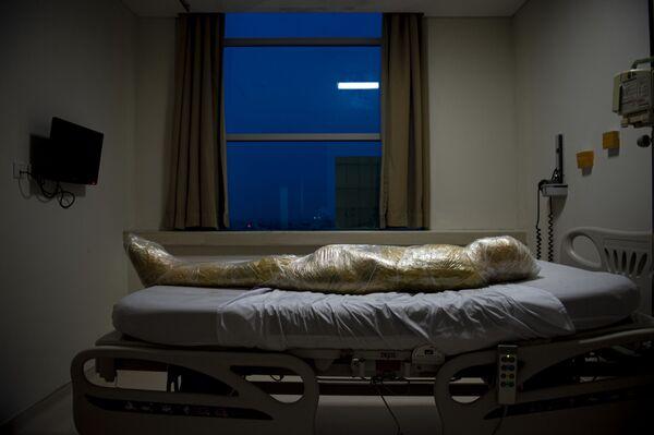 Oběť koronaviru zabalená do žlutých igelitových pytlů a obalů určených na likvidaci infekce leží na posteli pro zemřelé pacienty v Indonésii. - Sputnik Česká republika