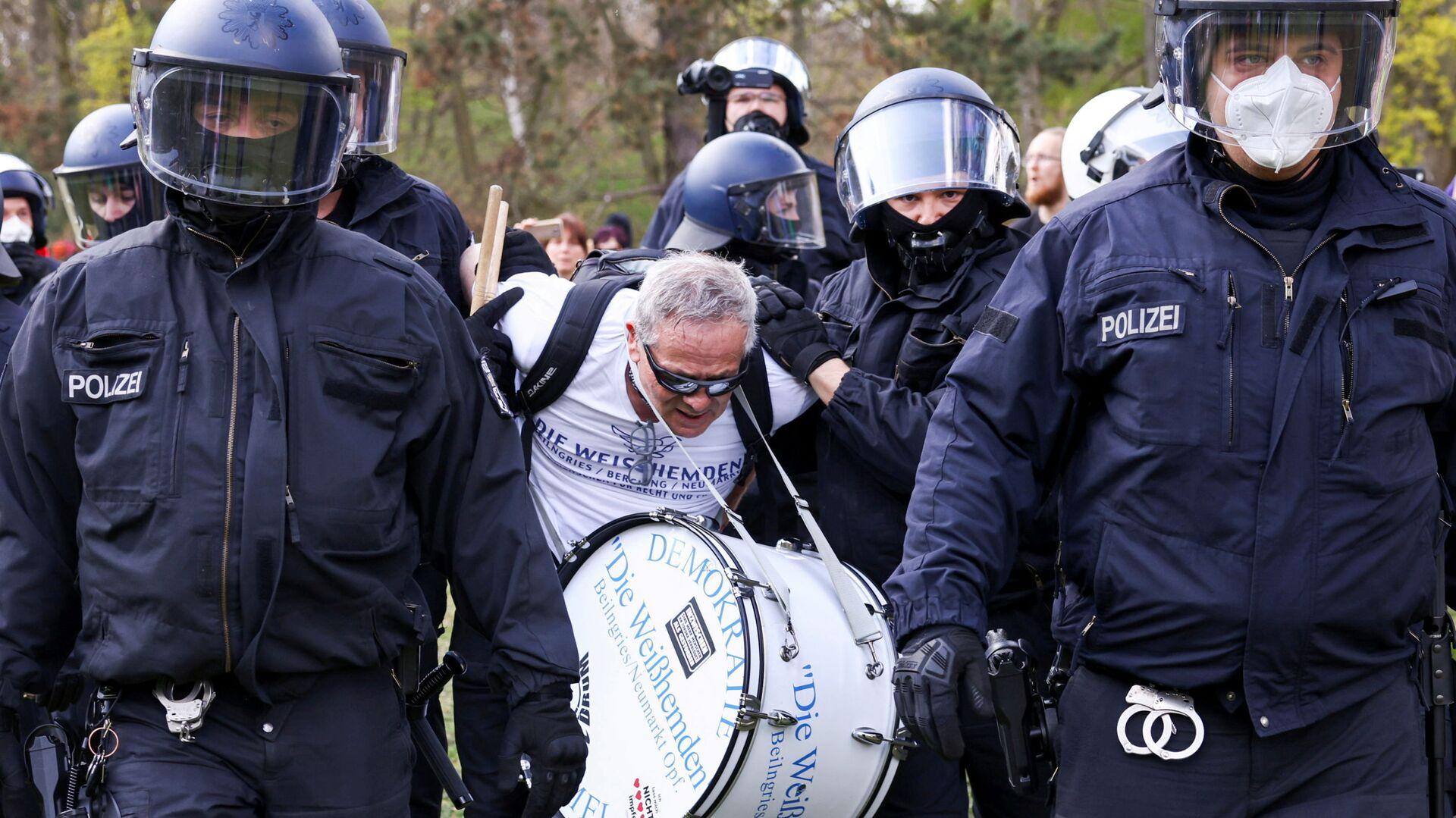 Сотрудники полиции задерживают участника акции протеста против политики правительства Германии по борьбе с пандемией коронавируса - Sputnik Česká republika, 1920, 21.04.2021