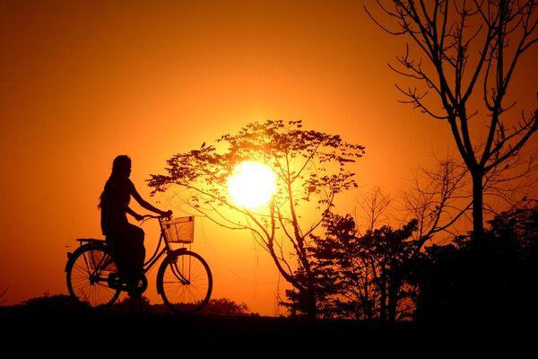 Indická dívka jezdí na kole během západu slunce v hlavním městě severovýchodního státu Tripura. - Sputnik Česká republika