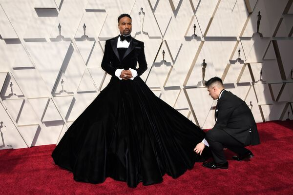 Herec Billy Porter na 91. ročníku předávání Oscarů v roce 2019. Horní část jeho outfitu se smokingem a motýlkem zcela odpovídala dress code, dále však začala provokace: místo kalhot zvolil bohatou dlouhou sukni - Sputnik Česká republika