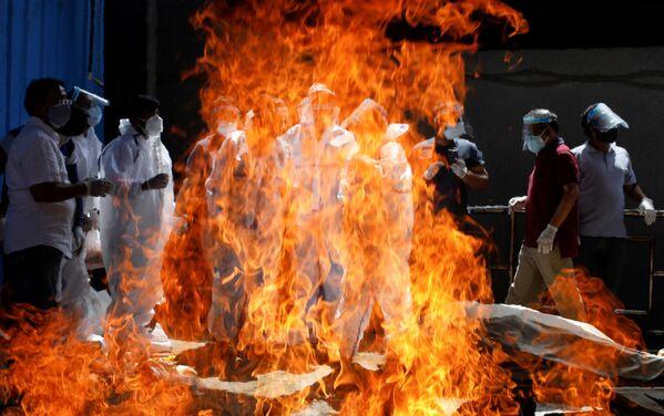Příbuzní u pohřebního ohně s tělem muže, který zemřel na koronavirus v Novém Dillí - Sputnik Česká republika