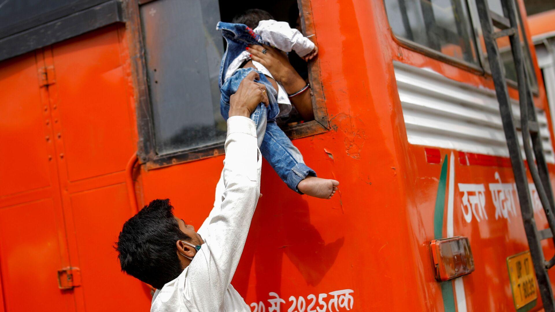 Рабочий-мигрант передает своего сына в окно автобуса, чтобы вернуться в свою деревню из-за шестидневной изоляции, Индия - Sputnik Česká republika, 1920, 10.08.2021