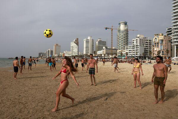 Lidé hrají fotbal na pláži v Tel Avivu - Sputnik Česká republika