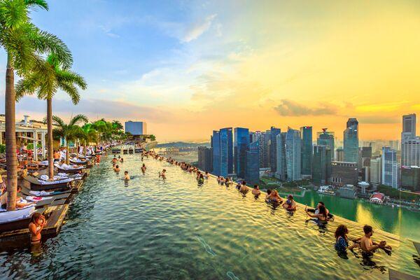 Bazén při západu slunce v Skyparku, který se tyčí nad hotelem Marina Bay Sands v Singapuru - Sputnik Česká republika