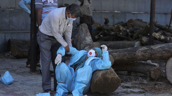 Родственник человека, умершего от COVID-19, во время кремации в Джамму, Индия - Sputnik Česká republika