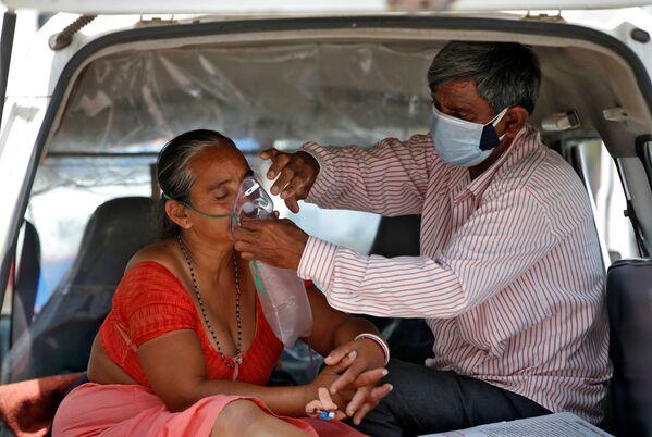 Muž upravuje kyslíkovou masku své ženě během čekání v autě na přijetí do nemocnice s covidem-19 k léčení, Indie - Sputnik Česká republika