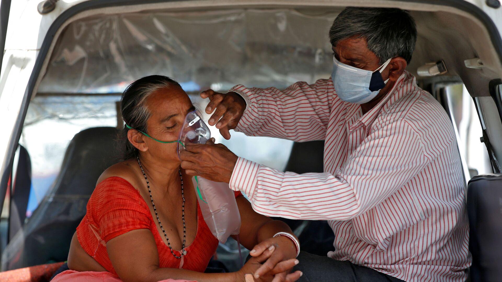 Muž upravuje kyslíkovou masku své ženě během čekání v autě na přijetí do nemocnice s covidem-19 k léčení, Indie - Sputnik Česká republika, 1920, 02.05.2021